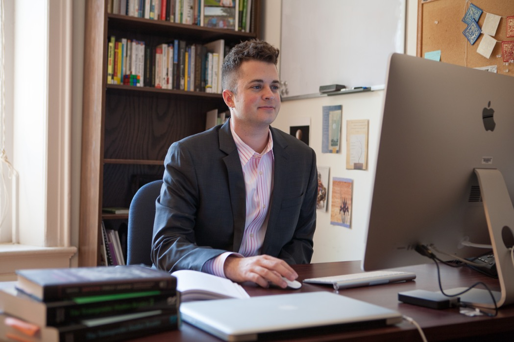 [Photo of Dr. KJ Rawson, working on a computer wearing a button up shirt and blazer]