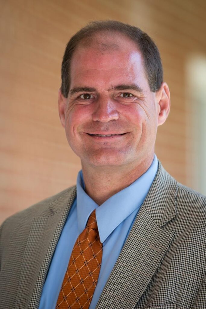 Portrait of Ian Danielsen, Assistant Professor at Longwood University. Ian is wearing a blue button up shirt with an orange tie and a plaid blazer.